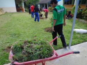 MENCOM sedang merapikan rumput sekitar kelas XII IPS 2